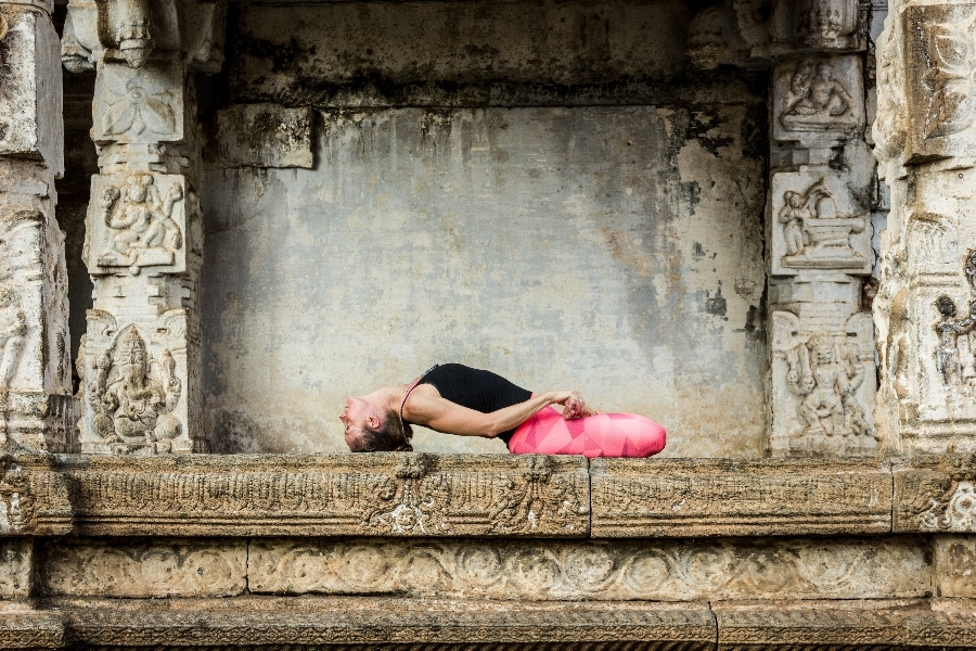Yogi woman in matsyasana pose with pink leggings and hands holding feet in lotus in Srirangapatna temple, Karnataka, India. Yoga teacher practicing in Hindu temple